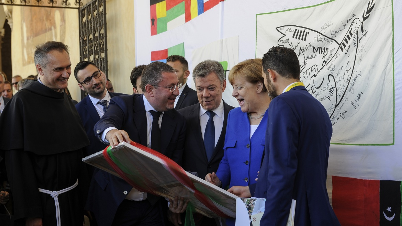 Angela Merkel riceve la Lampada della Pace e firma la Bandiera Auxilium
