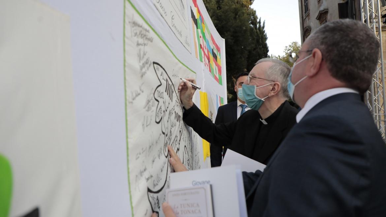 Il cardinale Pietro Parolin firma la Bandiera della Pace Auxilium